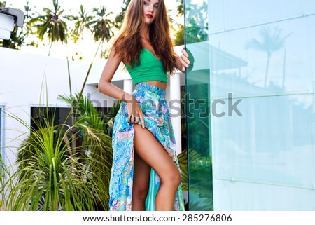 Young gorgeous stylish woman wearing luxury silk evening dress, posing at hotel,enjoy her vacation in hot tropical island, evening sunlight. - stock photo
