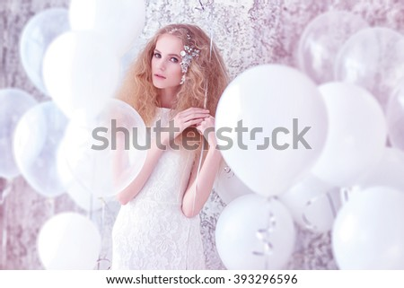 Young gorgeous woman, bride, blond long curly hair, studio decoration, white dress, balloons, soft colours - stock photo