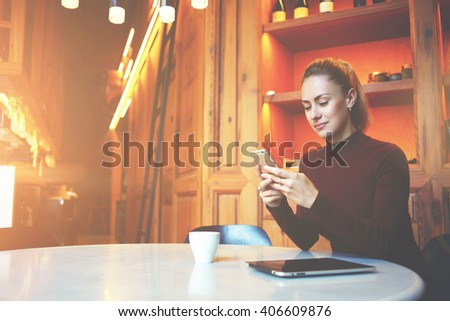Young gorgeous woman is using smart phone for chat with her friends while is sitting at the table in modern coffee shop interior,attractive female student is resting in contemporary university library - stock photo