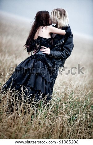Young goth couple kissing outdoors. Contrast colors. - stock photo
