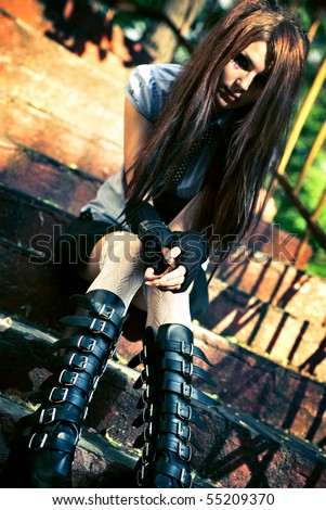 Young goth woman sitting on stairs. Focus on hands. - stock photo