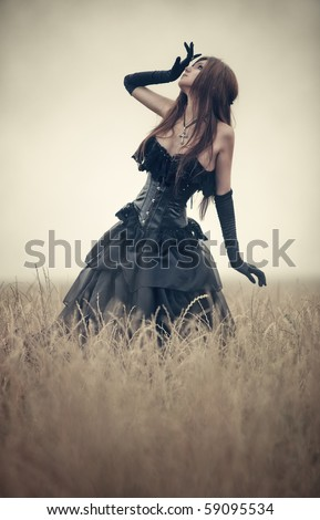 Young goth woman walking on field. - stock photo