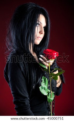 Young goth woman with red rose. On red background. - stock photo