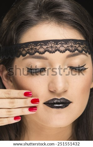 young gothic beautiful woman with eyes closed wearing black makeup and red nails - stock photo