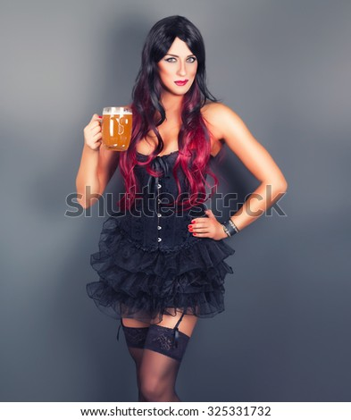 Young gothic woman in corset with mug of beer in hand - stock photo