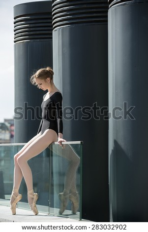 Young graceful ballerina in black bathing suit on a background o - stock photo