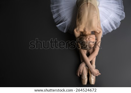 Young, graceful ballerina sitting on the floor on a black background in a studio in the slope face touching knees. Close-up.