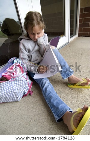 Young grade school age girl does school work outside of school entrance - stock photo