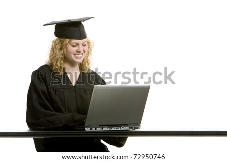 Young graduation girl on computer with white background - stock photo