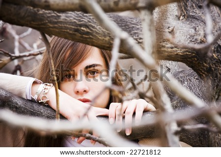 Young green eyed beauty between dead branches - stock photo