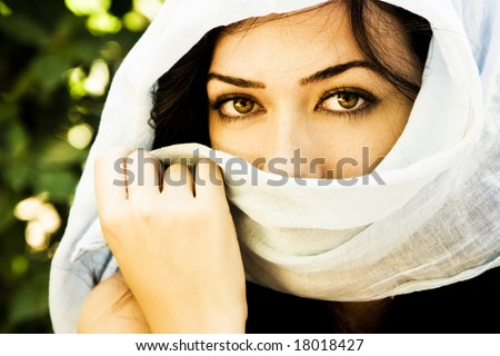 Young green eyed woman behind veil. - stock photo