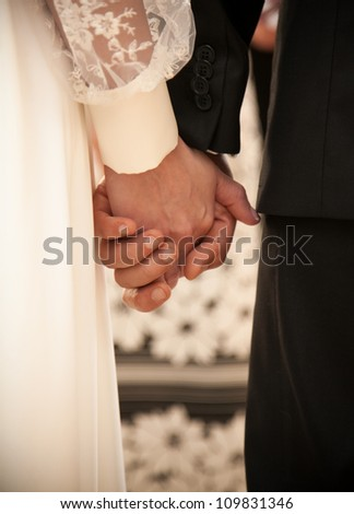 Young groom and bride holding hands - stock photo