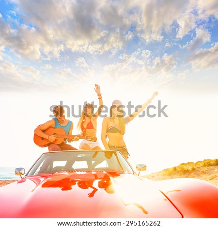 young group having fun on the beach playing guitar and dancing in a convertible car - stock photo