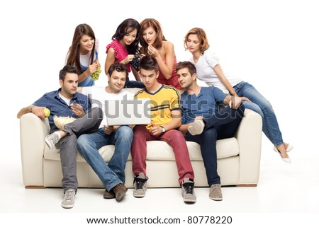 young group of friends sitting on couch looking at laptop