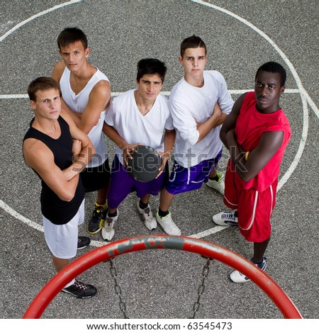 Young group of guys under a basketball hoop with stylish street clothes.