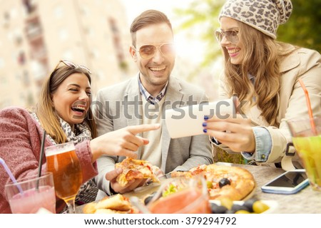 Young group of laughing people eating pizza and having fun - stock photo