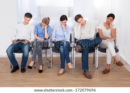 Young Group Of People Sleeping On Chair In A Waiting Room - stock photo