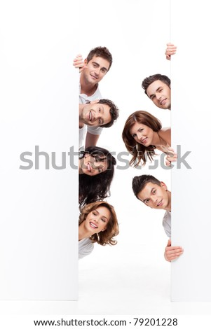 young group of people smiling behind advertising banner