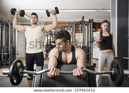 Young group of people training at gym, biceps and shoulder exercises: curl scott and shoulder lifting. - stock photo