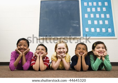 Young group of students lying on floor in classroom. Horizontally framed shot. - stock photo