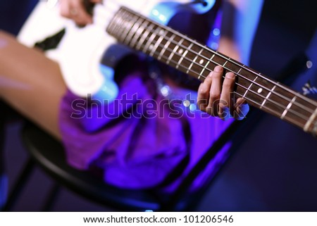Young guitar player with instrument performing in night club - stock photo