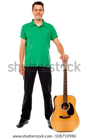 Young guitarist standing with guitar isolated on white background - stock photo