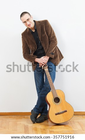 young guitarist standing with his guitar