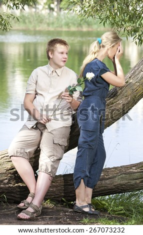 Young guy and girl on the nature near lake, reconciliation after quarrel