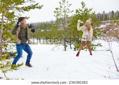Young guy and his girlfriend throwing snowballs at one another in the forest - stock photo