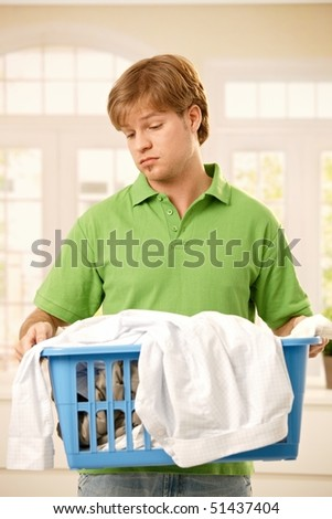 Young guy bored of housework holding a basket of clothes to do washing.