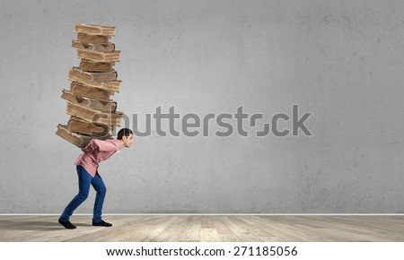 Young guy carrying pile of old books - stock photo