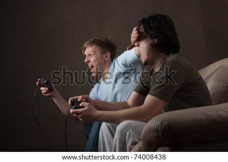 young guy covering friend's eyes while playing video games on gray background - stock photo