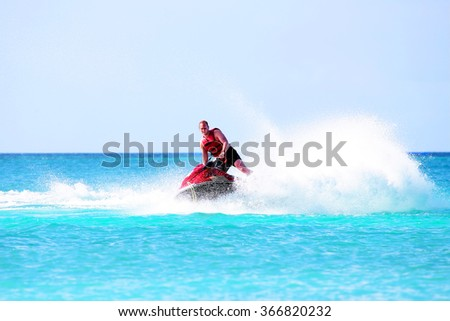 Young guy cruising on a jet ski on the caribbean sea - stock photo