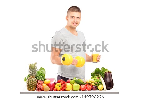 Young guy holding a dumbell and glass of fresh orange juice behind a pile of different fruits isolated on white background