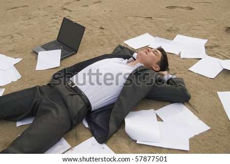 young guy in a business suit is on the beach among the scattered papers
