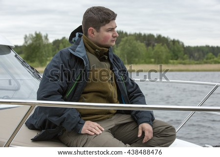 Young guy in a jacket with hood sits on the nose of the boat