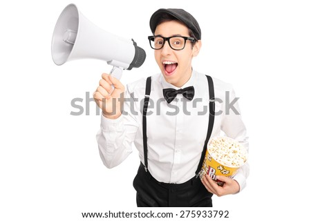 Young guy in artistic outfit holding a box of popcorn and speaking on a megaphone isolated on white background - stock photo
