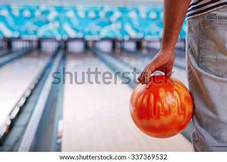Young guy in casualwear playing bowling - stock photo