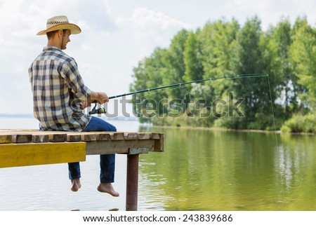 Young guy in hat sitting on bridge and fishing - stock photo