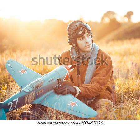 Young guy in vintage clothes pilot with an airplane model outdoors - stock photo