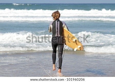 Young guy is going to surf in the atlantic ocean - stock photo