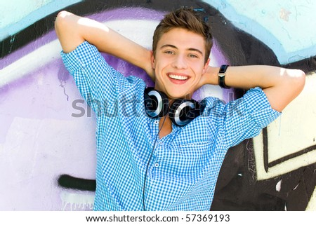 Young guy leaning on graffiti wall - stock photo