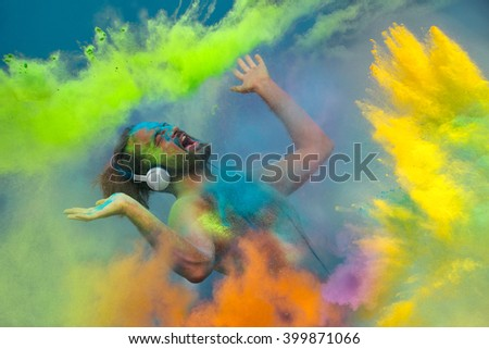 Young  guy listening music in headphones in the fog of colors during Holi celebration - stock photo