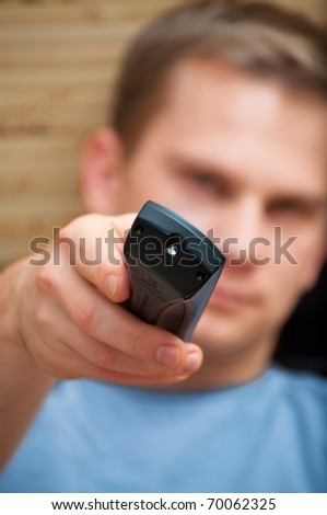 Young guy looking at camera while switching TV channels - stock photo