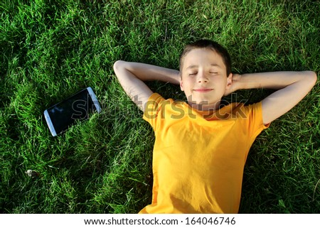 young guy lying on grass with a tablet outdoors - stock photo