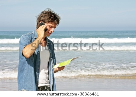 Young guy making a phone call on the beach - stock photo