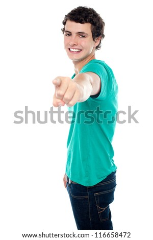 Young guy pointing you out with his stretched left arm. All on white background - stock photo