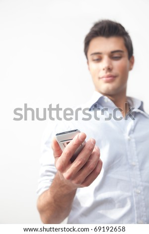 Young guy sending a sms with his mobile phone - stock photo