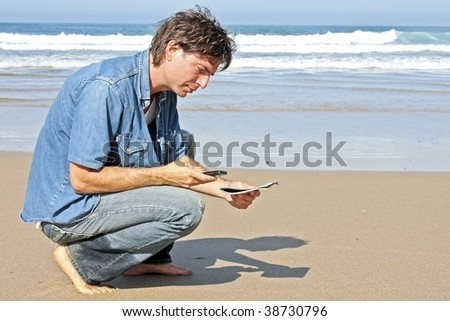 Young guy sending an text message at the beach - stock photo
