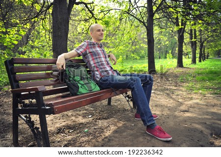 young guy sits on a bench in park